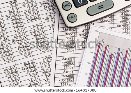a calculator is on a balance sheet figures are statistics. photo icon for sales, profit and cost. - stock photo