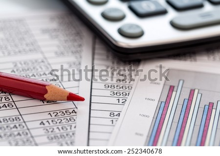 a calculator is on a balance sheet numbers are statistics. photo icon for sales, profits and costs. - stock photo