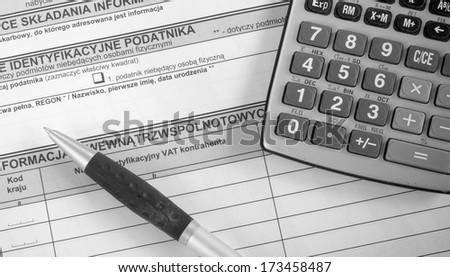 A calculator, pen, and financial statement