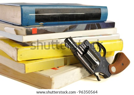 A 38 caliber pistol stands in front of school textbooks, isolated on white, focus on gun barrel - stock photo