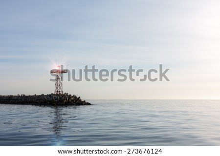 a calm cold blue and tranquil ocean surface with a harbour warning light at the end of a pier with sunlight reflected off the light. - stock photo