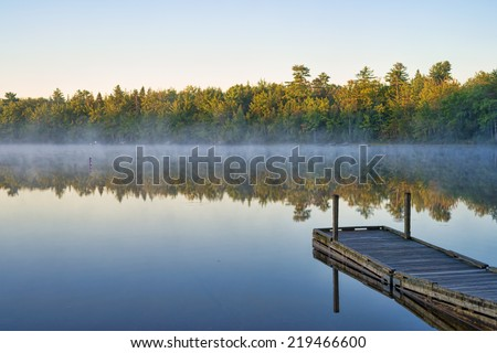 A calm early morning mist hanging above the water with forest and trees and a pier in the foreground at Toddy Pond, Maine. - stock photo