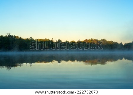 A calm early morning mist hanging above the water with the sun just touching the tops of the forest and trees at Toddy Pond, Maine. - stock photo