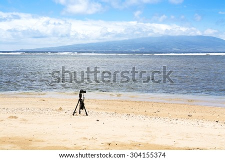 A camera and tripod on a deserted beach set to capture the ambiance of an empty natural wonder, with the island of Oahu outlining the horizon.  - stock photo