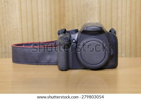 A camera on wooden table - stock photo