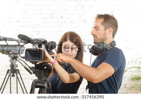 a cameraman and a young woman with a movie camera - stock photo