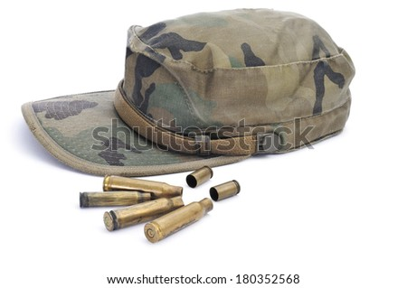a camouflage cap and some con a white background - stock photo