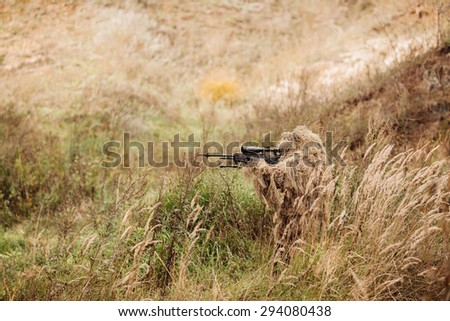 A camouflaged sniper sitting in the field aiming through his scope - stock photo