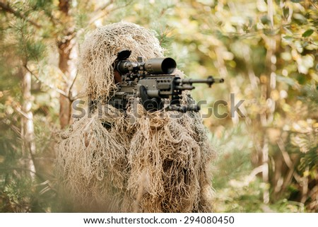 A camouflaged sniper sitting in the woods aiming through his scope - stock photo