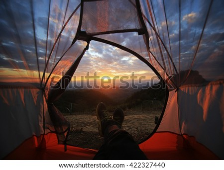 A camping tent glows under sunset to a night sky  Outdoor Camping adventure - stock photo