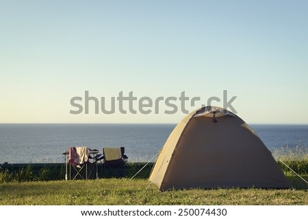 A camping tent is mounted facing the sea. Chairs and a table invite to contemplate the ocean. - stock photo