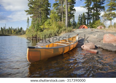 A campsite with a yellow canoe on a rocky shore of a Boundary Waters lake in Minnesota