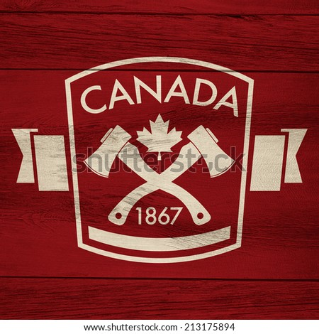 A Canadian lumberjack crest on a rustic wooden background. - stock photo