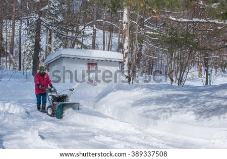 A Canadian man operating a snow throwing machine on a winter day after a snowstorm dumped 8 inches of snow.  Man operating a snow blower in Canada.  - stock photo
