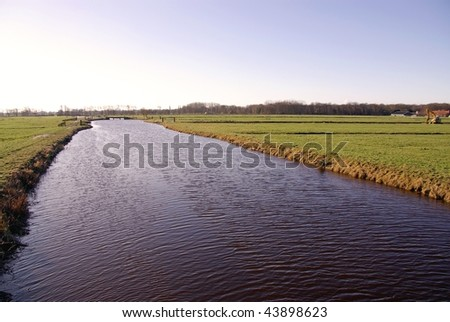 A canal between the meadows of farmers - stock photo