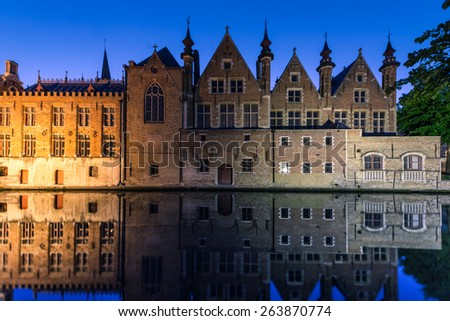 A canal reflects the buildings of the historic city of Bruges - stock photo