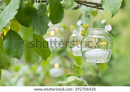 a candle in a glass with water hanging on a tree in the garden - stock photo