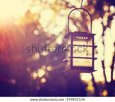 a candle lantern hanging in front of the summer sun during sunset toned with a retro vintage instagram filter effect app or action - stock photo