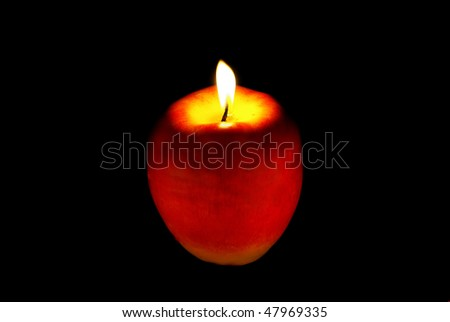 A candle on an apple.