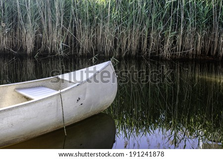 A canoe floats on a creek with the reflections of tall marsh grasses on the water