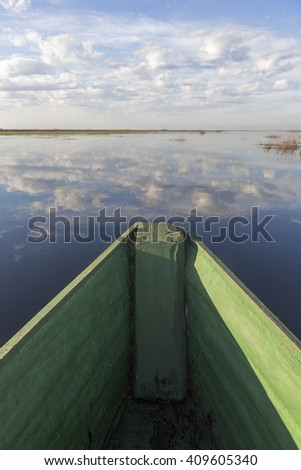 A canoe sails calm waters, with the sky reflected on water  - stock photo