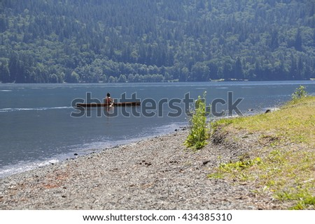 A canoeist in a traditional wooden canoe, paddles near a lake shoreline/Canoeist/A canoeist in a traditional wooden canoe, paddles near a lake shoreline.  - stock photo