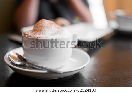 A cappuccino cup with milk foam and cinnamon - stock photo