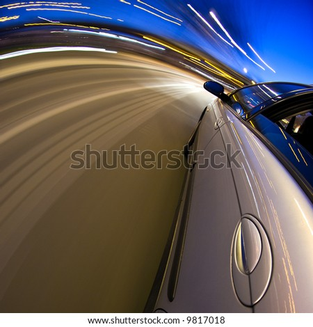 A car driving at high speed through a curved section of the motorway - stock photo