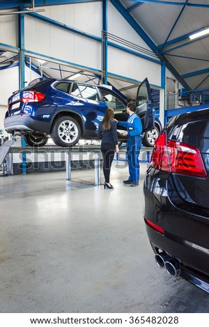 A car is lifted on a bridge in a car garage, the mechanic stands next to it with the owner - stock photo