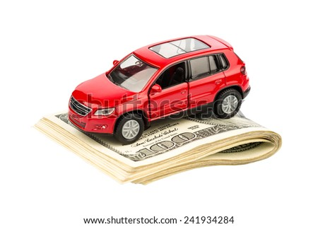 a car is on dollar bills. costs for the purchase of automobiles, gasoline, insurance and other car costs - stock photo