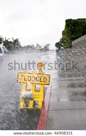 A car kicks up a pool of rainwater over a street flooded sign during bad, rainy weather. - stock photo