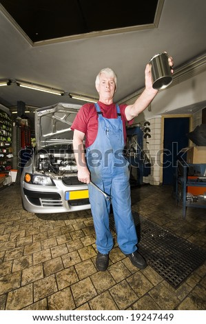 A car mechanic holding up a blank tin with a wrench in his hands posing in front of the car he's been working on inside a small garage - stock photo