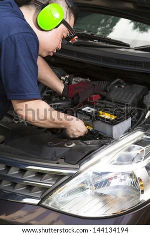 A car mechanic inspecting the car battery. - stock photo