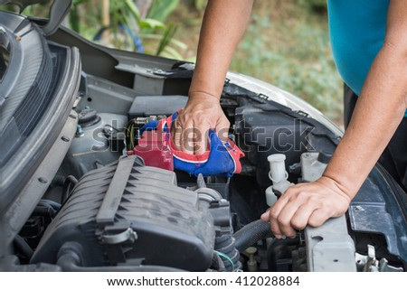 A car mechanic replaces a battery.  - stock photo