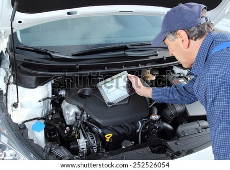 A car Mechanic with diagnostic equipment tablet - stock photo