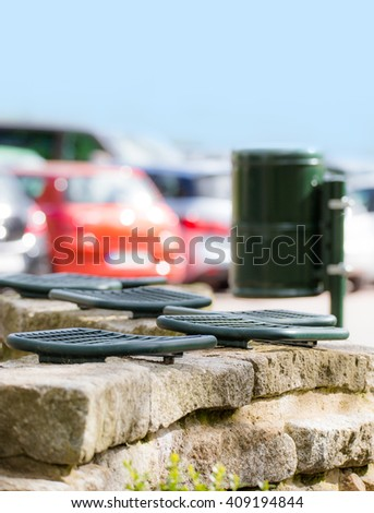 A car parking space with seating and trash can - stock photo