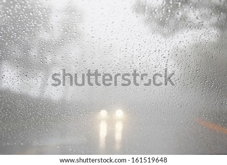 A car passing through path road in foggy and raining day, mist. - stock photo