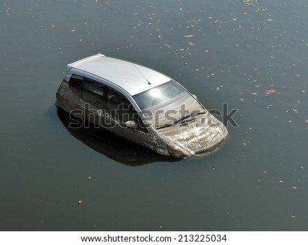 A Car Sits in a Flooded Car Park - Motor Vehicle Insurance Claim Themed Image - stock photo