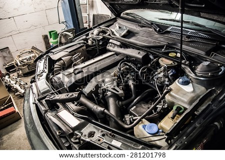 A car with an open hood in service - stock photo