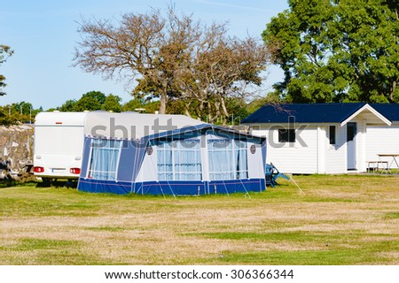 A caravan with awning tent attached to it is parked at a camping site. A small cabin is visible and behind the caravan is a dry tree. No person visible. Tent is closed. Fine warm day with sunshine. - stock photo