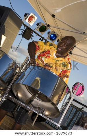 A Caribbean musician jamming on his steel drums. - stock photo