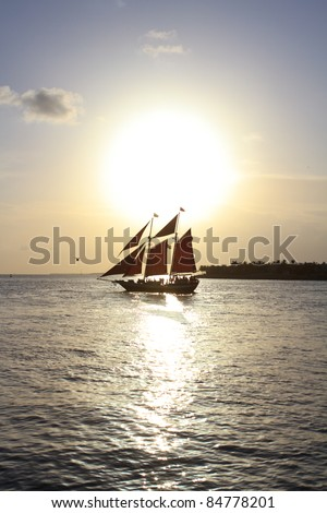 a caribbean pirate vessel with a sunset backdrop on the horizon - stock photo