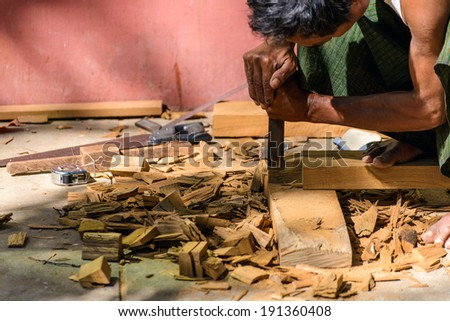 A carpenter chisel on a wooden plank - stock photo