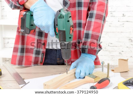 a carpenter drilling hole in plank, in his workshop - stock photo