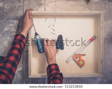 A carpenter is building a drawer in his workshop