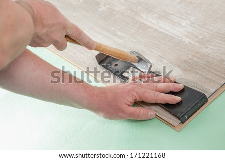 A Carpenter is fitting two pieces of Laminate with a hammer and a laminate tool. - stock photo