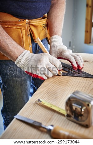 a carpenter making a measurement  - stock photo