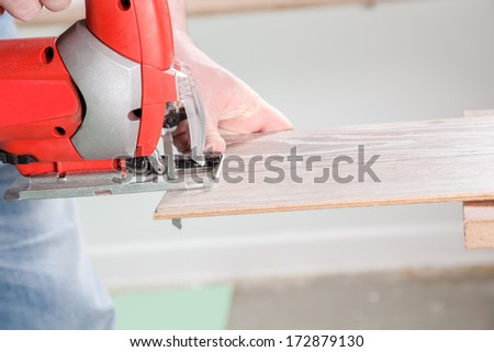 A Carpenter starts to saw a laminate plank with a jigsaw.