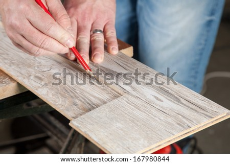 A carpenter use a cutted piece of laminate for marking an other one before cutting. - stock photo