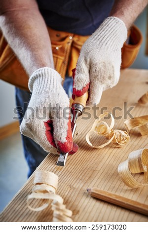 a carpenter using a chisel on a block of wood